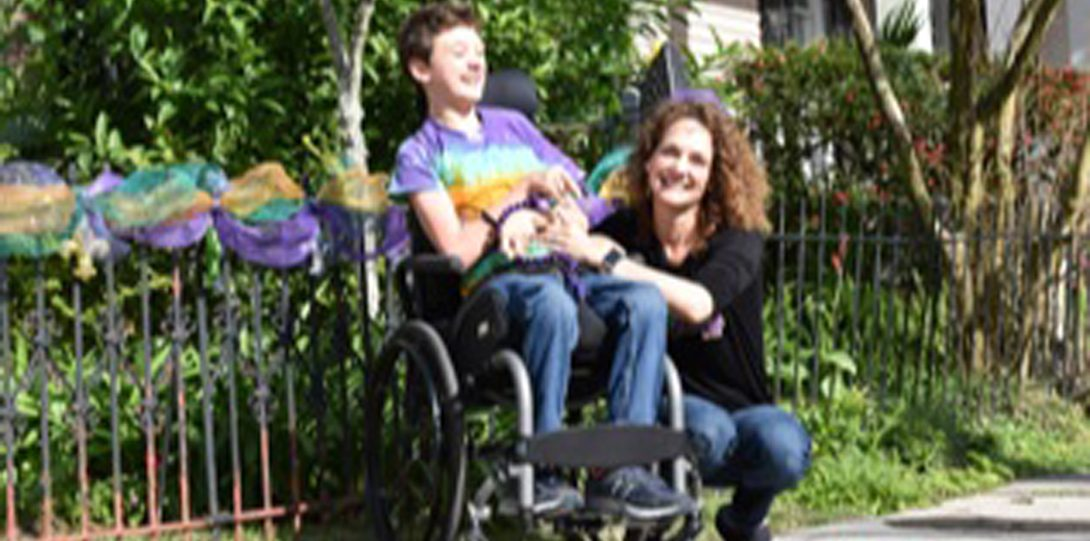 a woman and child in a wheelchair smiling at the camera